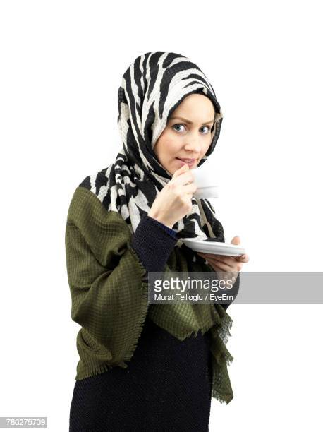 Portrait Of Young Woman In Hijab Having Coffee Against White Background