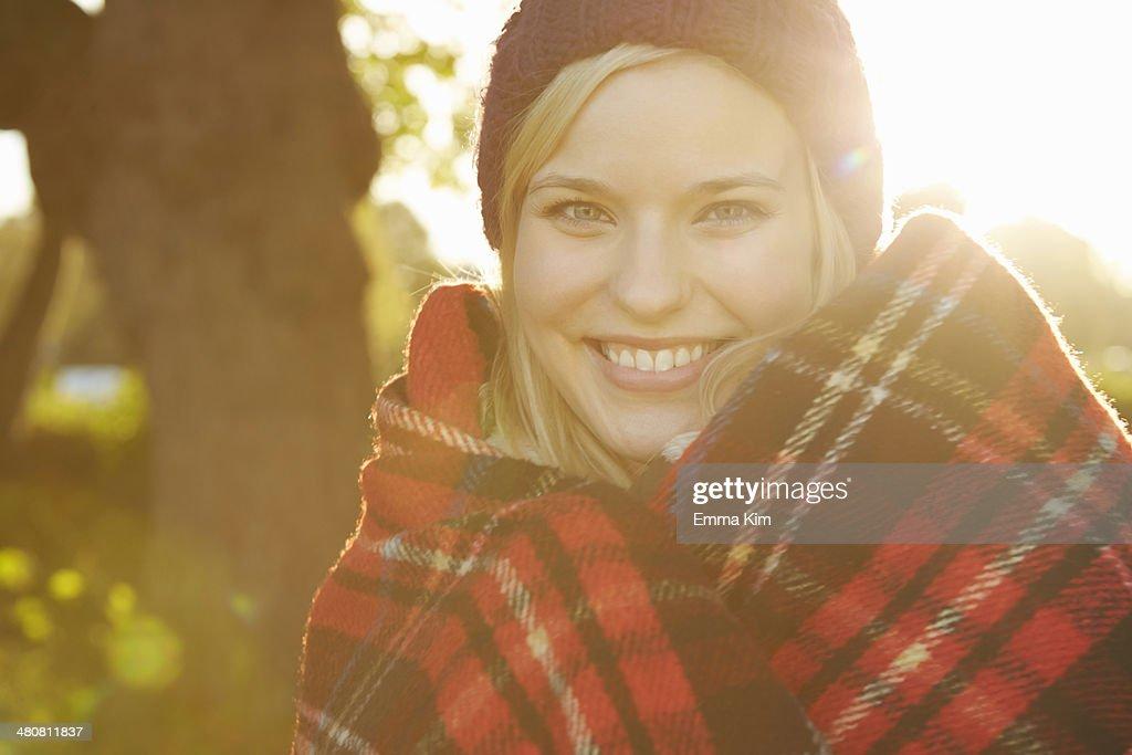 Portrait of young woman in park, tartan picnic blanket around shoulders