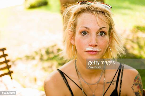 Portrait of young woman in park with coffee mustache