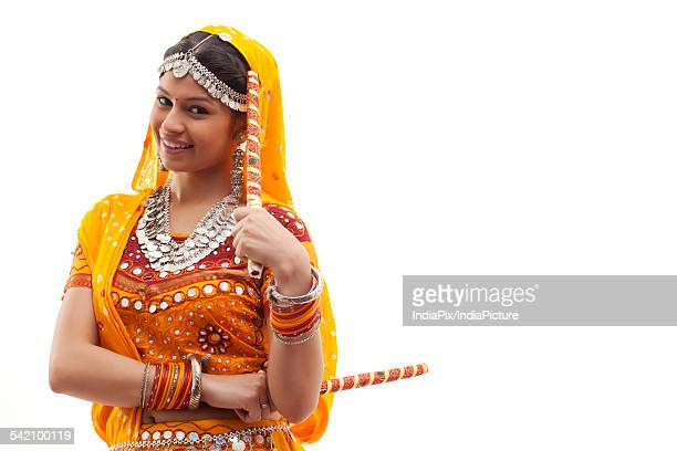 Portrait of young woman in traditional wear holding dandiyas isolated over white background