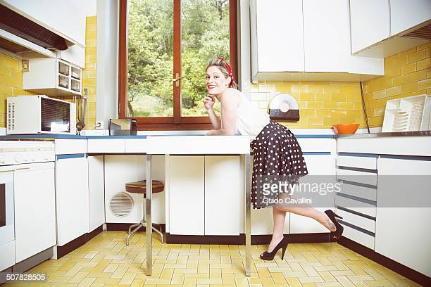 Portrait of young woman in vintage clothes in vintage kitchen