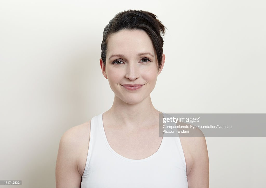 Portrait of young woman in white vest : Stock Photo