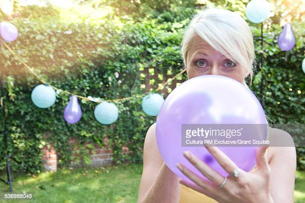 Portrait of young woman inflating balloon for garden party