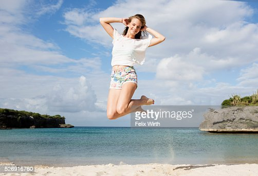 Portrait of young woman jumping on beach : Stock Photo