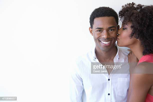 Portrait of young woman kissing man on cheek