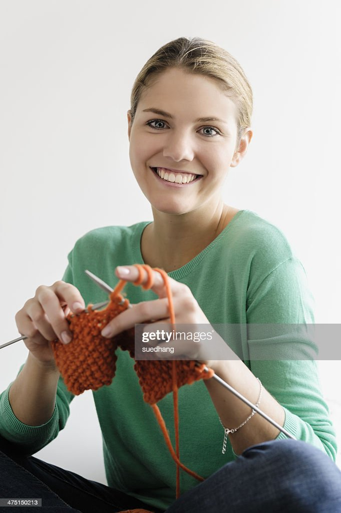Portrait of young woman knitting