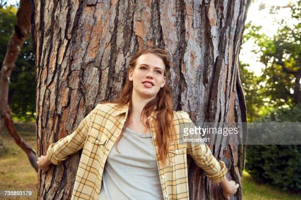 Portrait of young woman leaning against tree trunk
