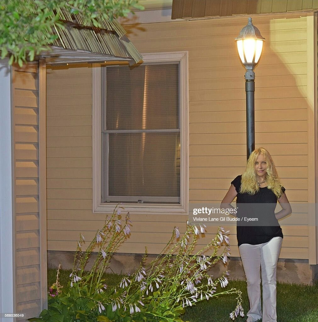 portrait of young woman leaning on illuminated light pole in yard