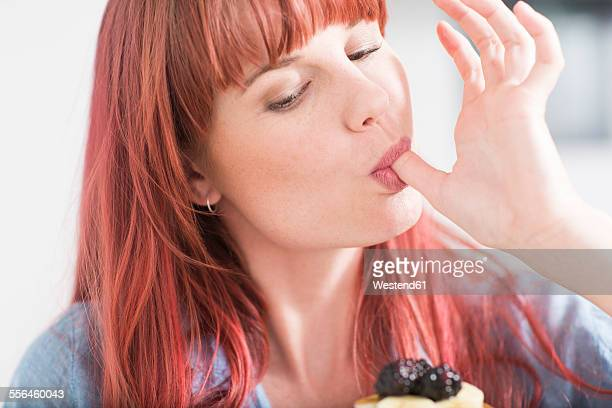 Portrait of young woman licking her finger