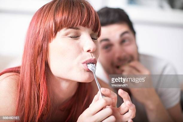 Portrait of young woman licking spoon