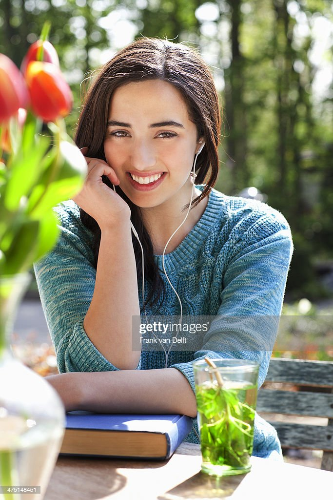 Portrait of young woman listening to earphones : Stock Photo