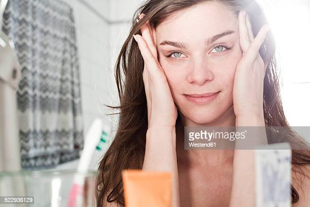 Portrait of young woman looking at her mirror image at the bathroom