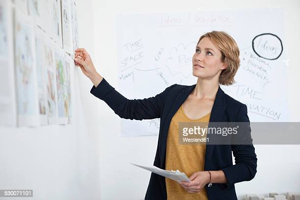 Portrait of young woman looking at wall with concepts in an office