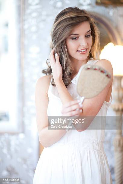 Portrait of young woman looking in hand mirror