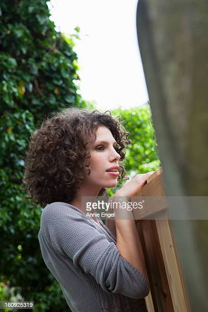 portrait of young woman looking over garden fence
