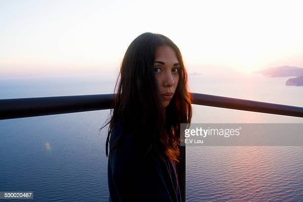 Portrait of young woman looking over her shoulder at coast, Marseille, France