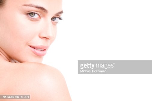 Portrait of young woman looking over shoulder, close-up : Stock Photo
