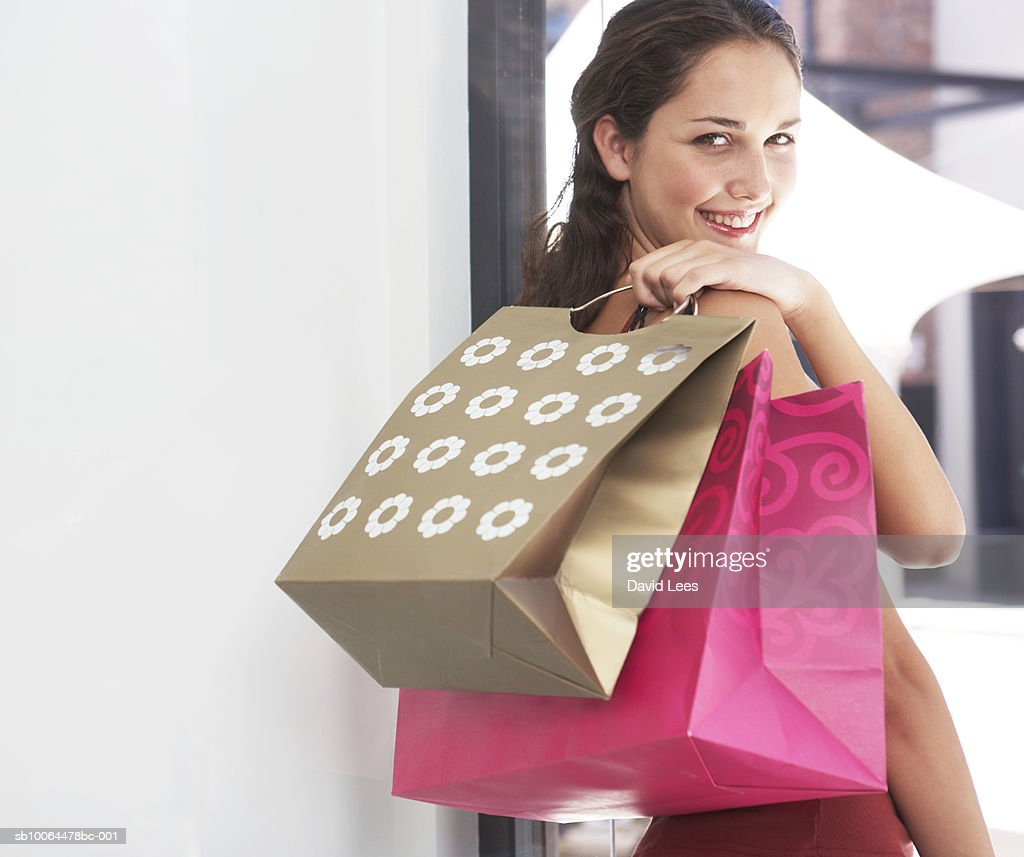 Portrait of young woman looking over shoulder, holding shopping bags : Stock Photo