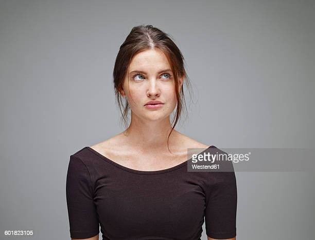 Portrait of young woman looking up in front of grey background