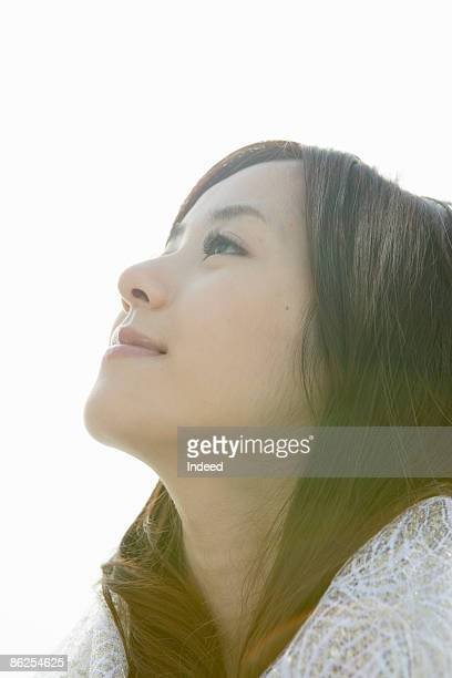 Portrait of young woman, looking up,