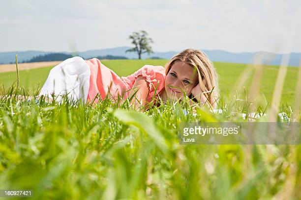 portrait of young woman lying in grass
