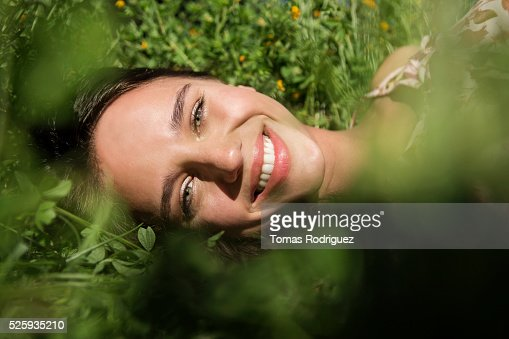 Portrait of young woman lying on grass : Bildbanksbilder