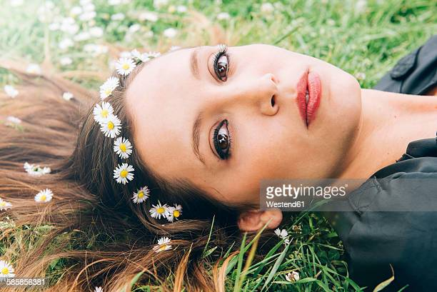 Portrait of young woman lying on grass with daisies in her hair