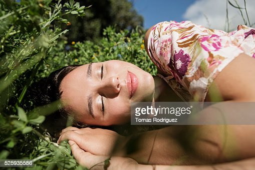 Portrait of young woman lying on grass with eyes closed : ストックフォト