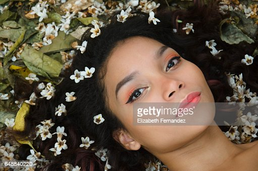 Portrait of young woman lying on meadow with flowers in her hair : Stock Photo