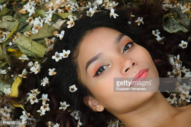 Portrait of young woman lying on meadow with flowers in her hair