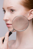 Portrait of young woman, magnifying glass on cheek