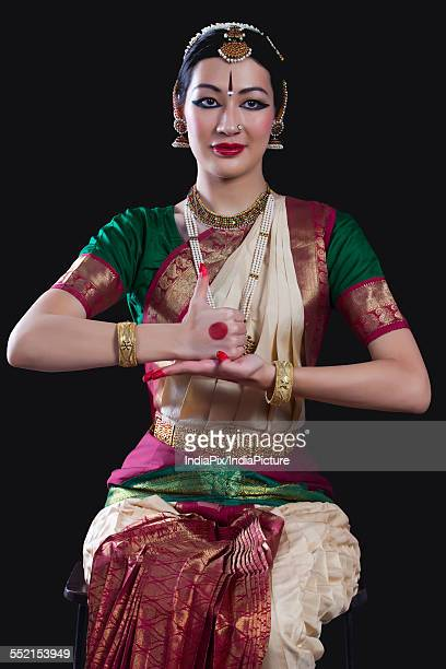 Portrait of young woman making Bharatanatyam gesture called Shivalingam on black background