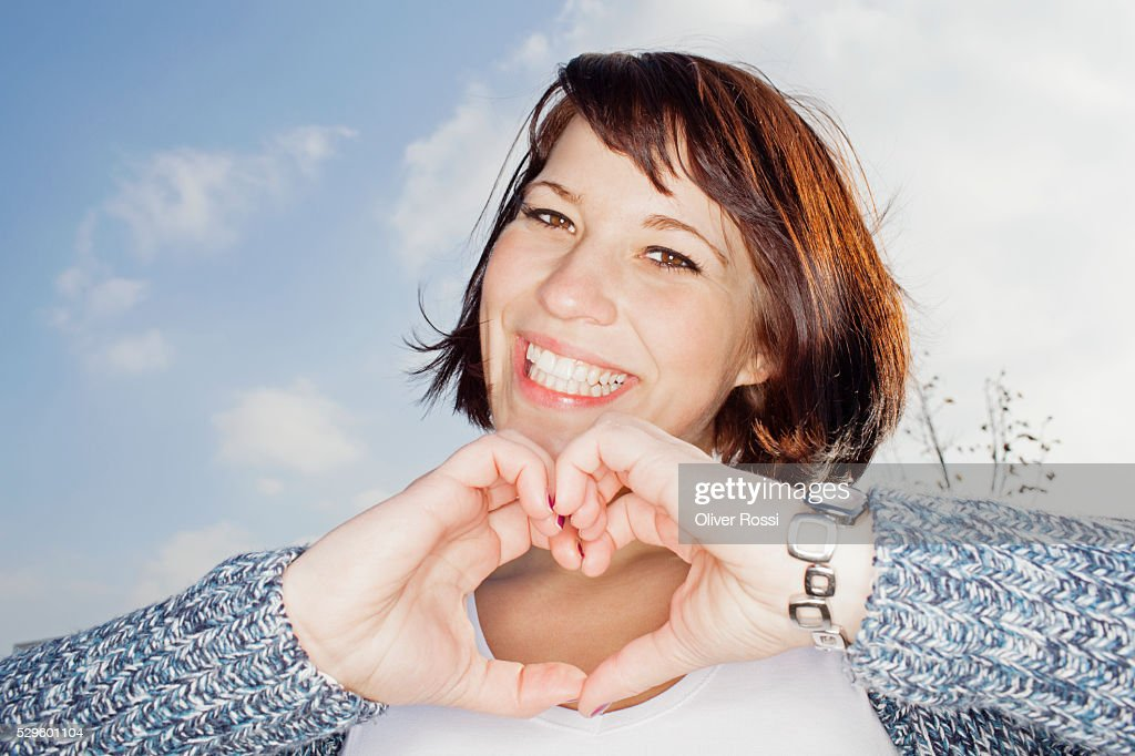 Portrait of young woman making heart shape : Stock-Foto