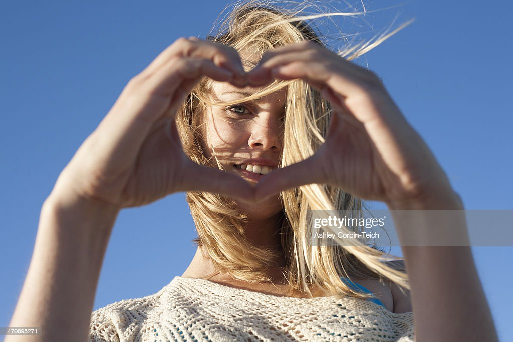 Portrait of young woman making heart sign, Breezy Point, Queens, New York, USA : Stock Photo