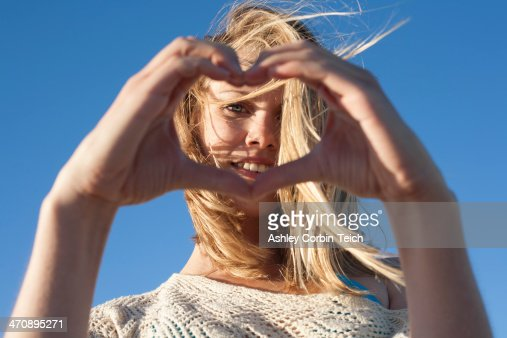 Portrait of young woman making heart sign, Breezy Point, Queens, New York, USA