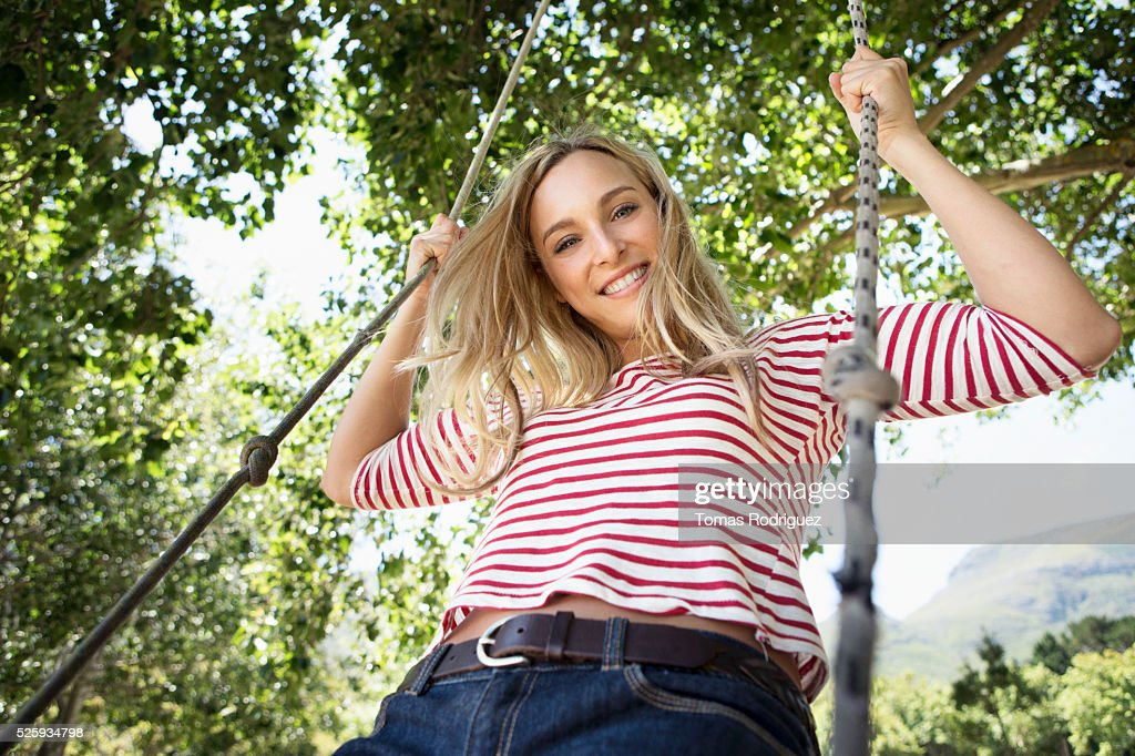 Portrait of young woman on swing : Stock Photo