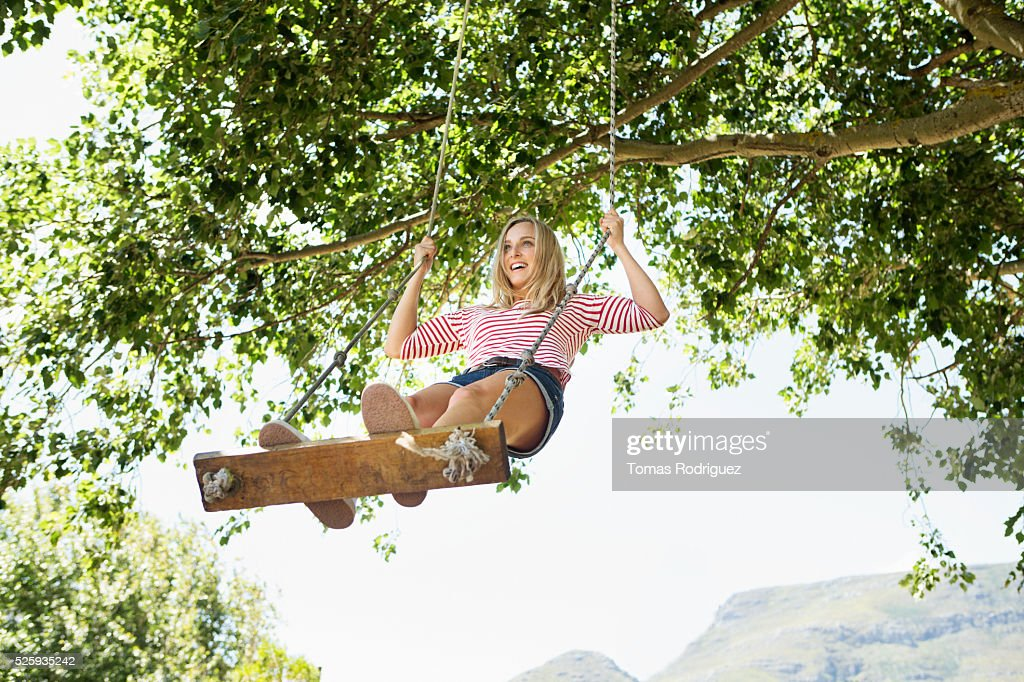 Portrait of young woman on swing : Stockfoto