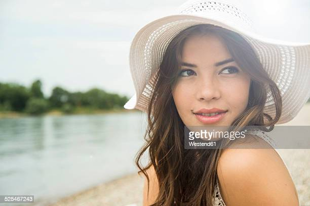 Portrait of young woman on the beach wearing white summer hat