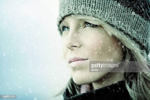 Porträt der jungen Frau außerhalb, während es schneien