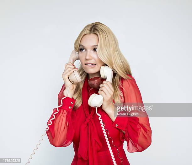 portrait of young woman overwhelmed by 3 phones