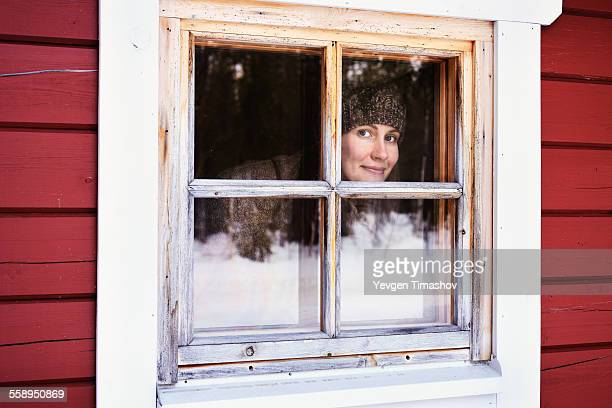 Portrait of young woman peering out of cabin window, Posio, Lapland, Finland