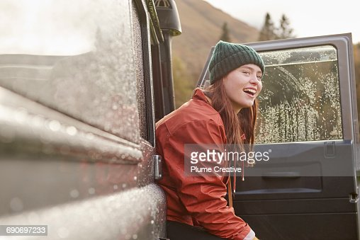 Portrait of young woman peering out of car