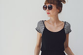 Portrait of young woman. Casual outfit. Black dress over a contrasting stripes t-shirt. Copy space.