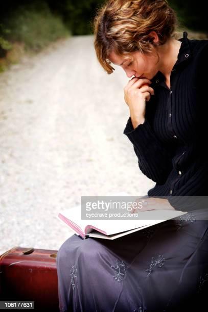 Ritratto di giovane donna lettura libro sulla Strada di campagna