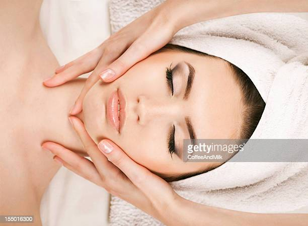 Portrait of young woman receiving facial massage