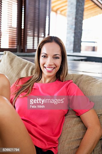 Portrait of young woman reclining on sofa : Stock-Foto