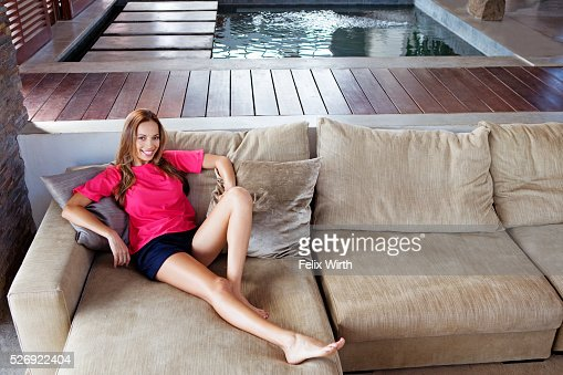 Portrait of young woman reclining on sofa : Stock Photo