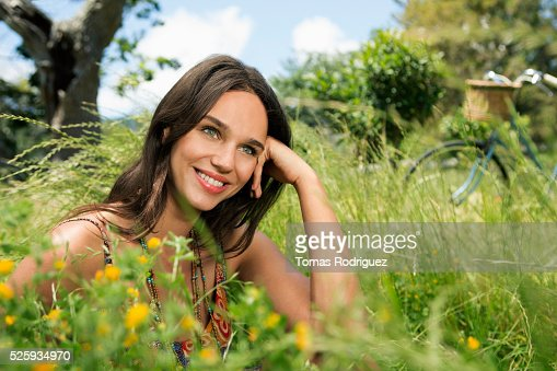 Portrait of young woman relaxing in field : Stock Photo