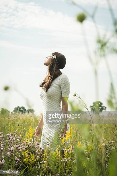 Portrait of young woman relaxing on flower meadow