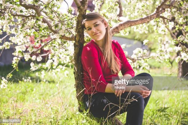 Porträt der jungen Frau ruht unter weiß blühende Baum auf Wiese